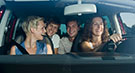 Das Bild zeigt lachende junge Leute in einem Auto (refer to: Risk behaviour of young drivers: The influence of peers)