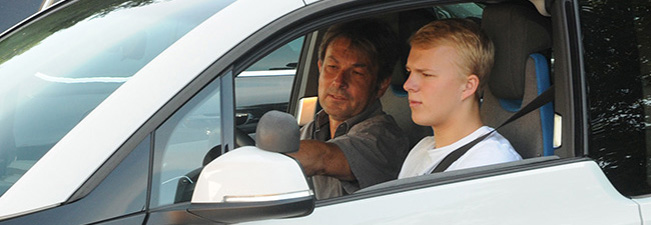 The picture shows a driving instructor and a young driver